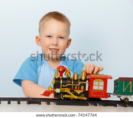Little boy playing with a toy locomotive on blue background - stock photo