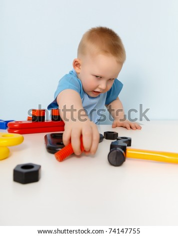 Little boy playing with a toy plastic constructor on blue background - stock photo