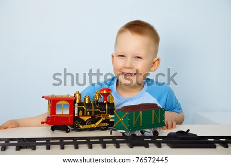 Little boy playing with a toy railway - stock photo