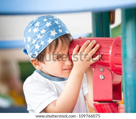 Little boy playing with a toy telescope at the playground - stock photo
