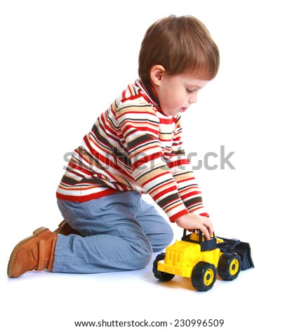 Little boy playing with a toy tractor.Isolated on white background.