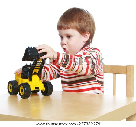 little boy playing with a toy tractor sitting at the table.Isolated on white background portrait. - stock photo