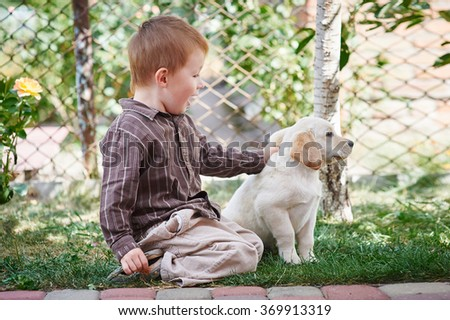 little boy playing with a white Labrador puppy.