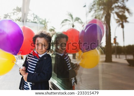 little boy playing with balloons beside a window reflection - stock photo