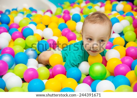 little boy playing with balls in the entertainment center - stock photo