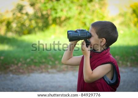 Little boy playing with binoculars - stock photo