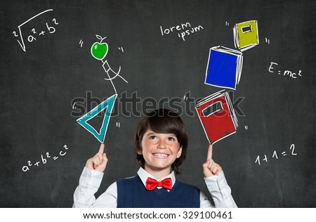 Little boy playing with books and school instruments. Portrait of happy boy smiling and looking up. Cheerful cute child indicates formulas with arms raised above the head. Education concept. - stock photo