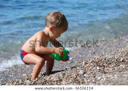 little boy playing with bucket on the beach - stock photo
