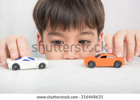 Little boy playing with car toy on  the table - stock photo