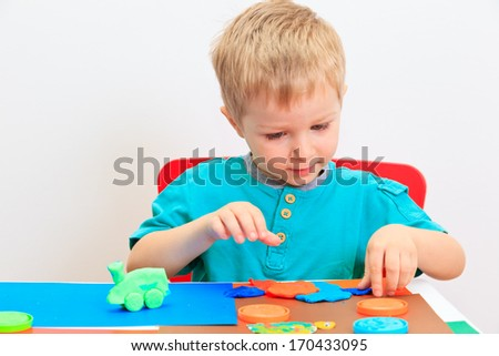 little boy playing with clay dough, education and daycare concept - stock photo