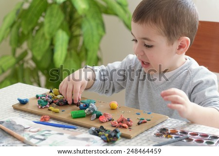 Little boy playing with clay, sculpting figures. - stock photo