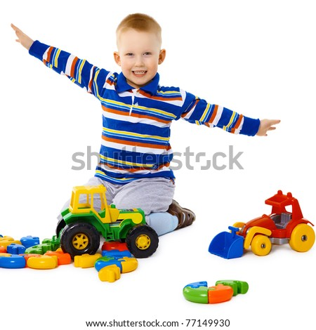 Little boy playing with color toys on floor - stock photo