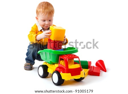 Little boy playing with colorful car toy isolated on white