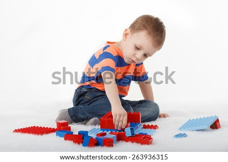 Little boy playing with designer on the floor on white background - stock photo