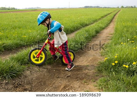 Little boy playing with his bike outdoors with a colorful safety helmet. - stock photo