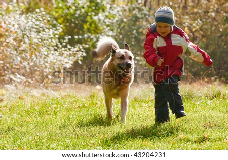 Little boy playing with his dog in autumn forest