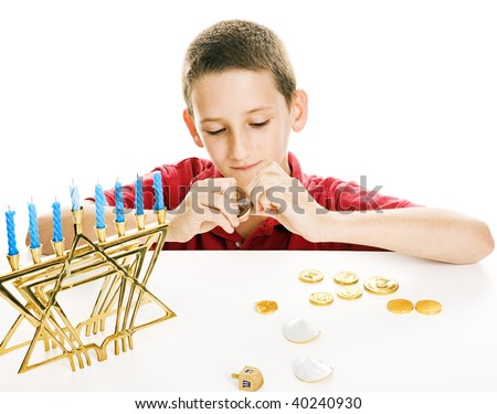Little boy playing with his dreidel and eating chocolate coins on Chanukah.  White background. - stock photo