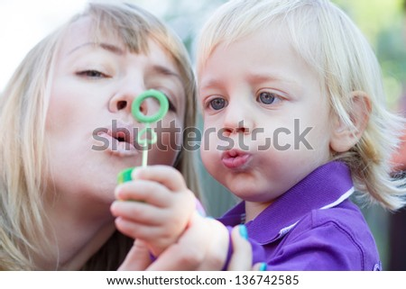 Little boy playing with his mother on the playground. Blowing bubbles togethers - stock photo