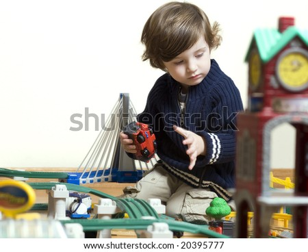 little boy playing with his new train set. Shallow DOF. - stock photo