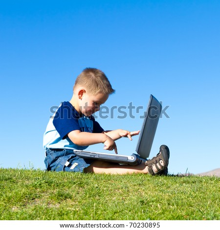 little boy playing with laptop - stock photo