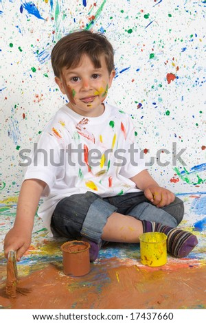 Little boy playing with painting with the background painted