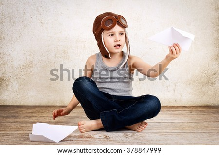 Little boy playing with paper airplanes - stock photo