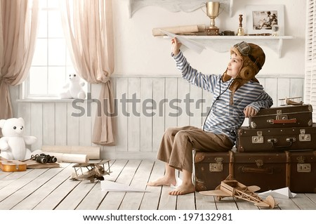 Little boy playing with paper airplanes in my room - stock photo