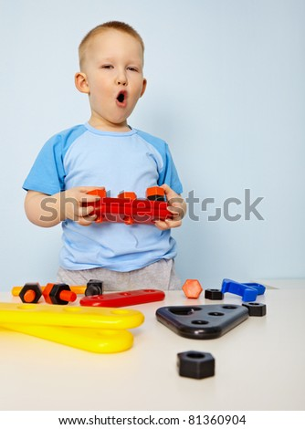 Little boy playing with plastic toys on blue background - stock photo