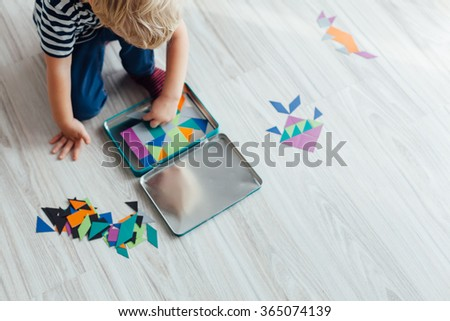 Little boy playing with puzzle on the floor - stock photo