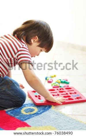 Little boy playing with puzzles on the floor - stock photo