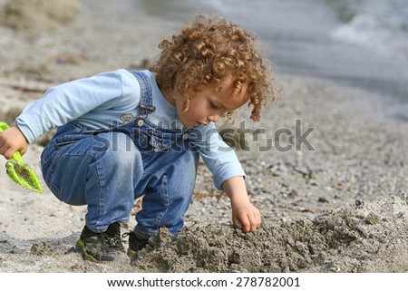 Little boy playing with sand on a beach by the lake