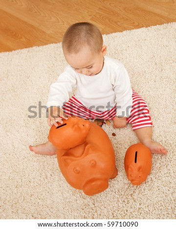 Little boy playing with several clay piggy banks on the floor - stock photo