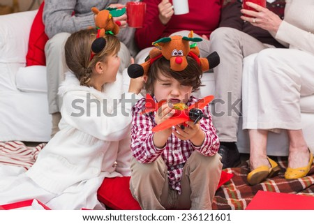 Little boy playing with toy airplane during christmas time at home in the living room - stock photo