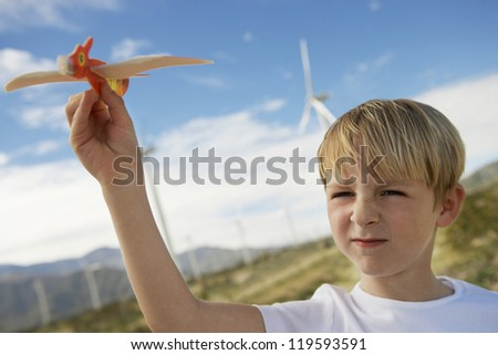 Little boy playing with toy glider at windmill farm - stock photo