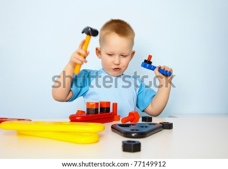 Little boy playing with toy tool - stock photo