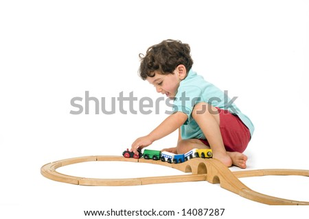 little boy playing with toy train isolated on white - stock photo