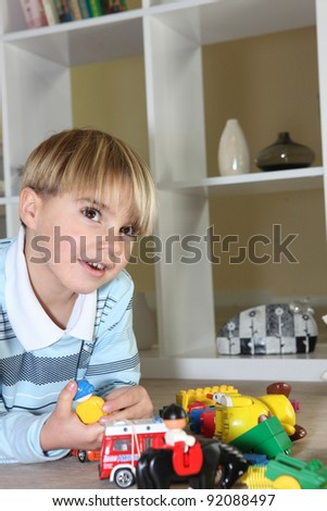 Little boy playing with toys - stock photo