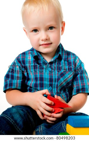 little boy playing with toys on a white background - stock photo