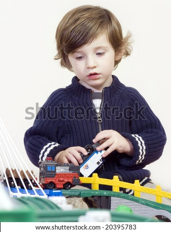 little boy playing with train set. Shallow DOF. - stock photo