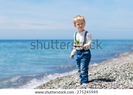 Little boy plays a ship against the sea - stock photo