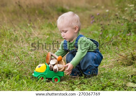 little boy plays a toy car with mushrooms - stock photo