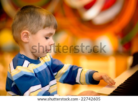 Little boy plays brown piano.