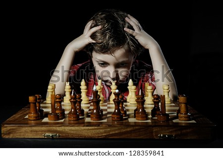 little boy plays chess - stock photo