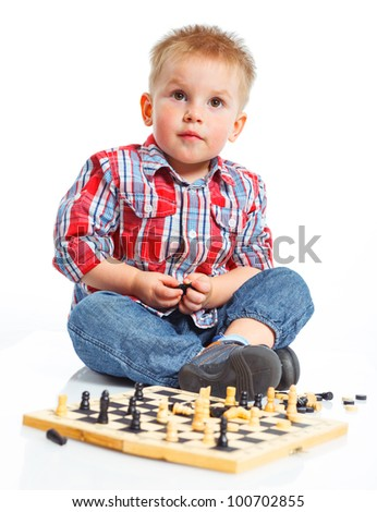 Little boy plays chess. Isolated on white. - stock photo
