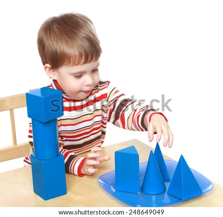 Little boy plays cubes and cones sitting at the table, Montessori kindergarten.Isolated on white background, Lotus Children's Center - stock photo