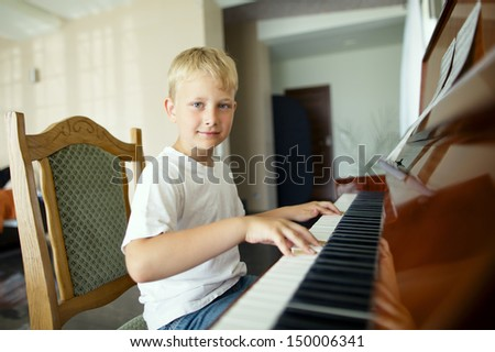 little boy plays piano - stock photo