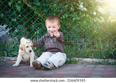 Little boy plays with a white puppy Labrador. - stock photo