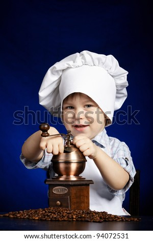 little boy plays with coffee mill
