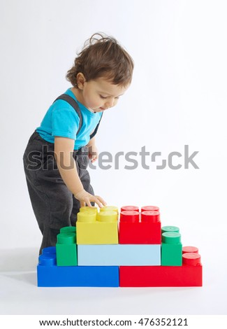 little boy plays with colorful cubes