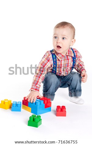 little boy plays with cubes